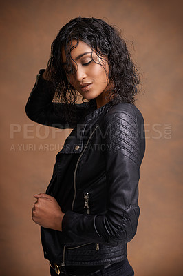 Buy stock photo Studio shot of an attractive young woman in a leather jacket against a brown background