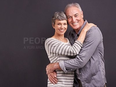 Buy stock photo Studio portrait of an affectionate elderly couple against a gray background