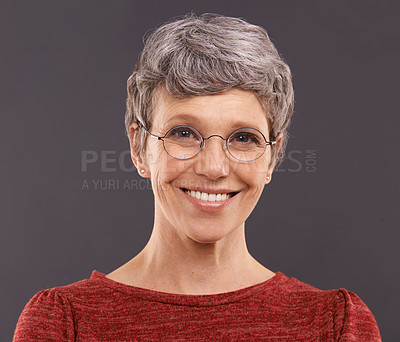Buy stock photo Studio portrait of a happy elderly woman wearing glasses against a gray background