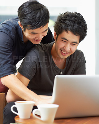 Buy stock photo Shot of a young gay couple using a laptop indoors