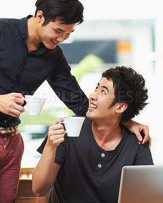 Buy stock photo Shot of a young gay couple drinking coffee while sitting with a laptop
