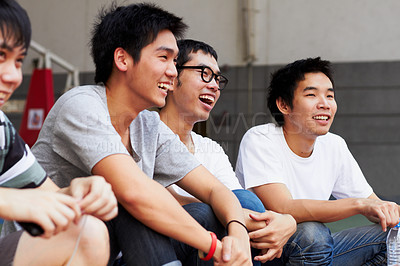 Buy stock photo A group of asian youths laughing together while sitting outdoors