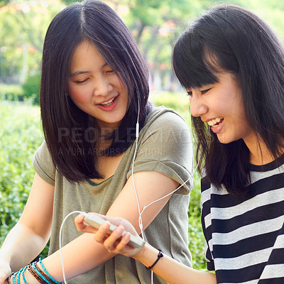 Buy stock photo Shot of two attractive young women listening to music together outside