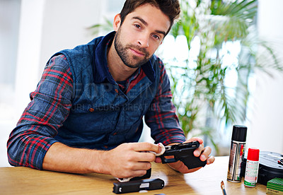 Buy stock photo Portrait of a man cleaning his gun