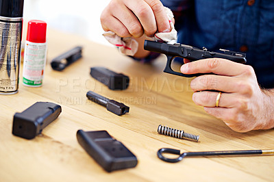 Buy stock photo Cropped view of a man cleaning his gun