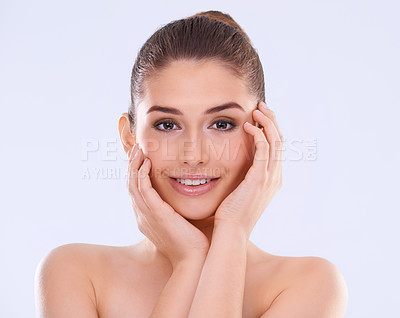 Buy stock photo Studio portrait of a beautiful young woman touching her flawless skin