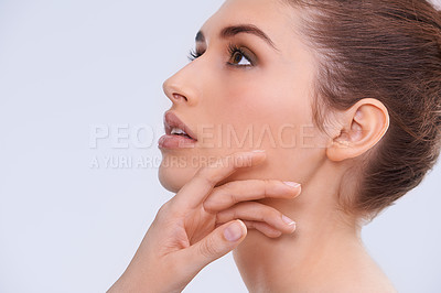 Buy stock photo Studio shot of a beautiful young woman touching her flawless skin