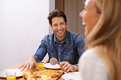 Buy stock photo A happy couple sitting down to eat pizza together