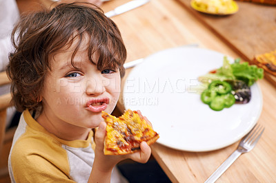 Buy stock photo A little boy eating pizza at the dinner table