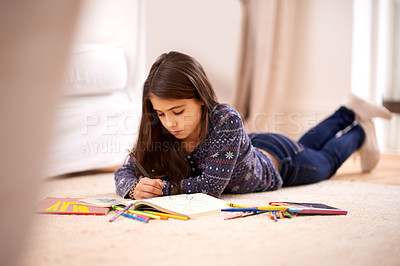 Buy stock photo A young girl coloring while lying on the floor