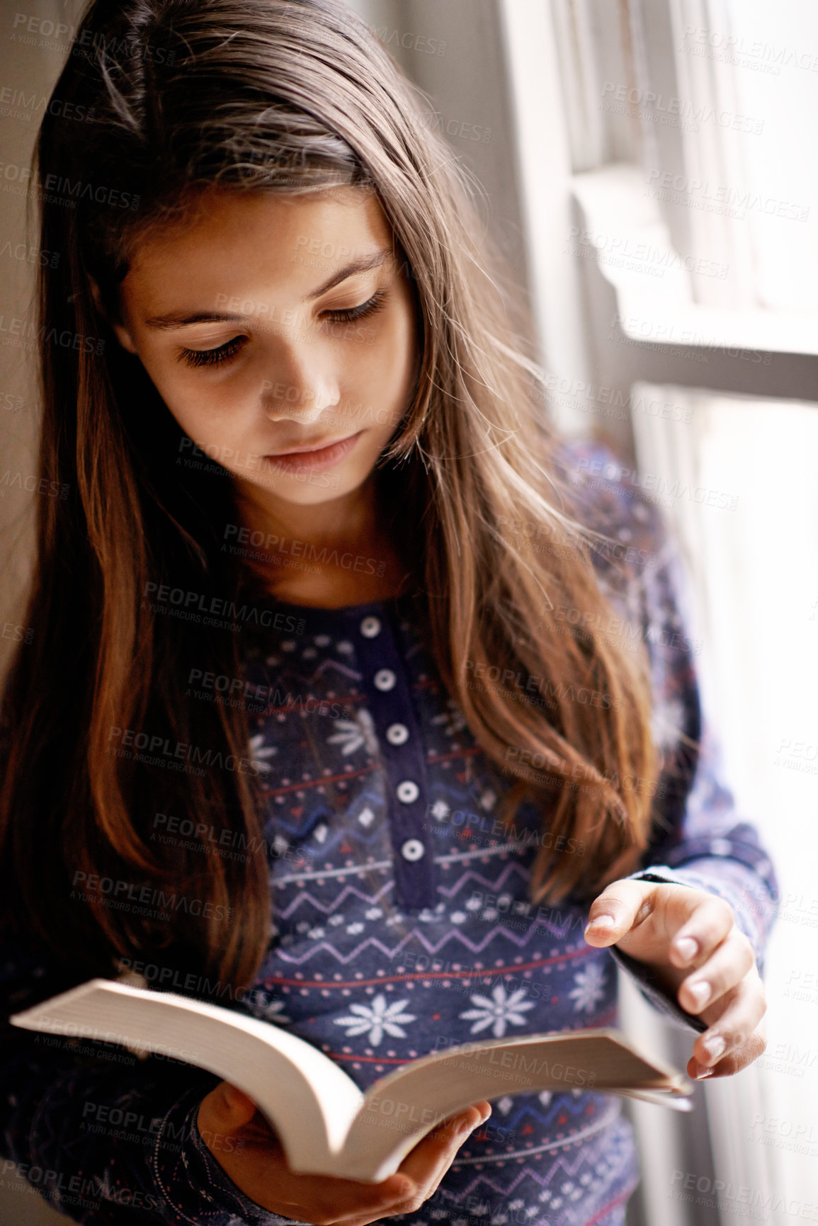 Buy stock photo Portrait of a cute little girl reading at home
