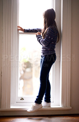 Buy stock photo Rearview shot of a young girl looking out of a window