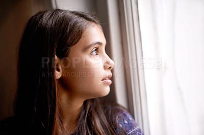 Buy stock photo Shot of a little girl looking out of a window