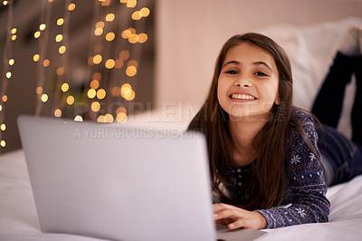 Buy stock photo Portrait of a cute little girl using her laptop while lying on her bed