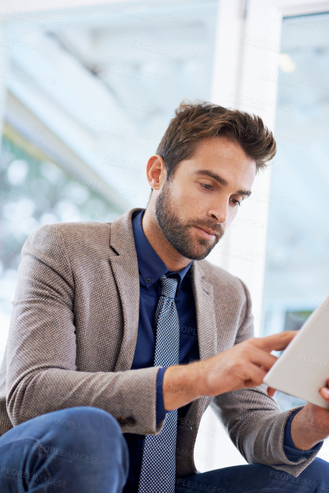 Buy stock photo Shot of a businessman using his digital tablet
