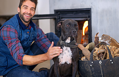 Buy stock photo Shot of a young man and his dog indoors beside a fireplace