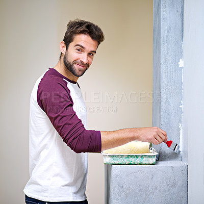 Buy stock photo Photo of an attractive young man painting a wall indoors
