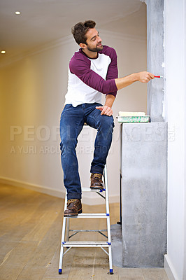 Buy stock photo Photo of an attractive young man painting a wall indoors while sitting on a ladder