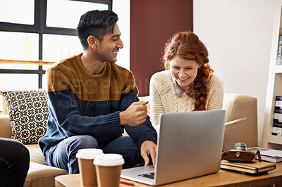 Buy stock photo Cropped shot of a young couple sitting on their laptop at a coffee shop