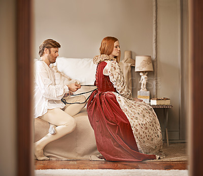 Buy stock photo Shot of a noble man undressing his wife in their bed chamber