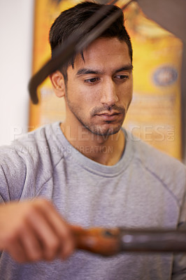 Buy stock photo Shot of a handsome young man operating heavy duty machinery
