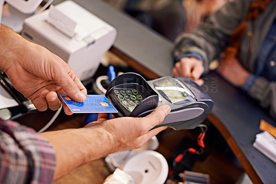 Buy stock photo Shot of a customer paying for their order with a debit machine in a cafe
