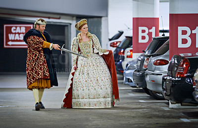 Buy stock photo A king and queen in a parking garage viewing cars suspiciously