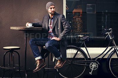 Buy stock photo Shot of a handsome young man in winter wear having a beverage at a sidewalk cafe