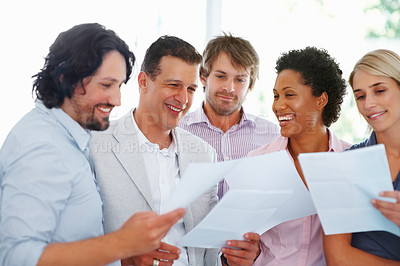 Buy stock photo Group of smiling young professionals looking at paper work