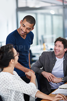 Buy stock photo Shot of a group of young coworkers talking at a deask