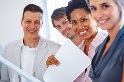 Buy stock photo View of team in row with focus on young woman holding paper