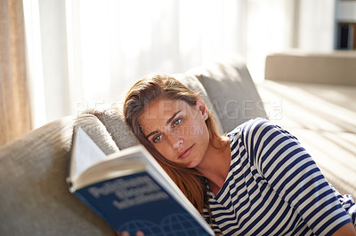 Buy stock photo Shot of a young woman reading a book on her sofa at home