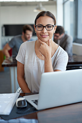 Buy stock photo Portrait of a young woman working on a laptop in an office