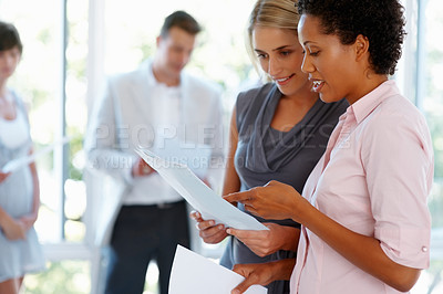 Buy stock photo Two business women going through the documents with team in background