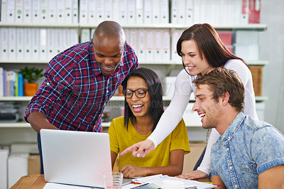 Buy stock photo Shot of a young designers laughing at a laptop at work in an office