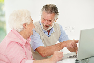 Buy stock photo Shot of a happy-looking senior couple working on a laptop together