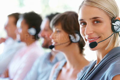 Buy stock photo Attractive female executive wearing headset with colleagues in background