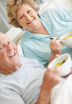 Buy stock photo Portrait of a senior couple smiling at the camera while eating breakfast in bed