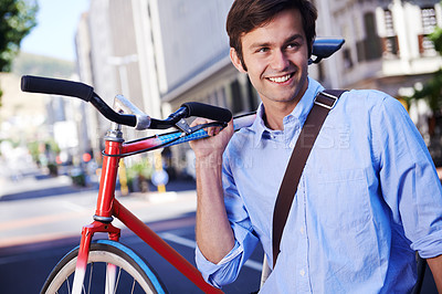 Buy stock photo A handsome young man carrying his bicycle in the city