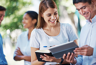Buy stock photo A group of people looking at  a digital tablet outdoors