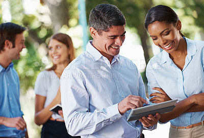 Buy stock photo A group of people looking at  a digital tablet outdoors with copyspace