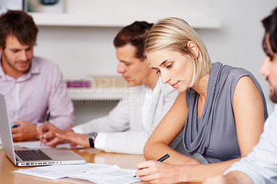 Buy stock photo Young female executive signing document with her team in office
