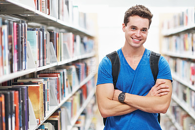 Buy stock photo Shot of a young man crossing his arms in the library corridor