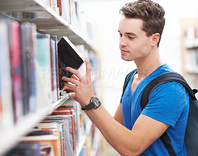 Buy stock photo Shot of a young man researching information for a new assignment