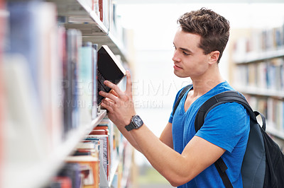 Buy stock photo Shot of a young man pulling a book of interest from the library shelf