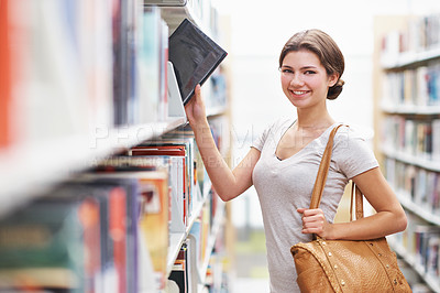 Buy stock photo Cropped shot of a young woman holding onto her handbag while researching