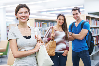 Buy stock photo Shot of three young students waiting in the campus library