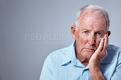Buy stock photo Studio portrait of a sad looking elderly man with his hand on his chin