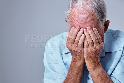 Buy stock photo Studio shot of a depressed elderly man with his head in his hands