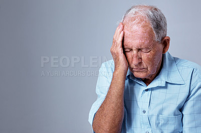 Buy stock photo Studio shot of an elderly man with a headache against a gray background